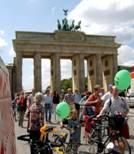 Menschen mit grünen Luftballons vor Brandenburger Tor