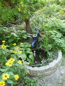 Brunnen mit Handpumpe und Staudensonnenblumen