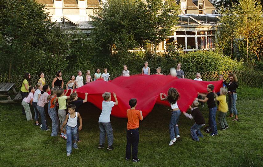 Kinder mit großem Tuch im Kreis
