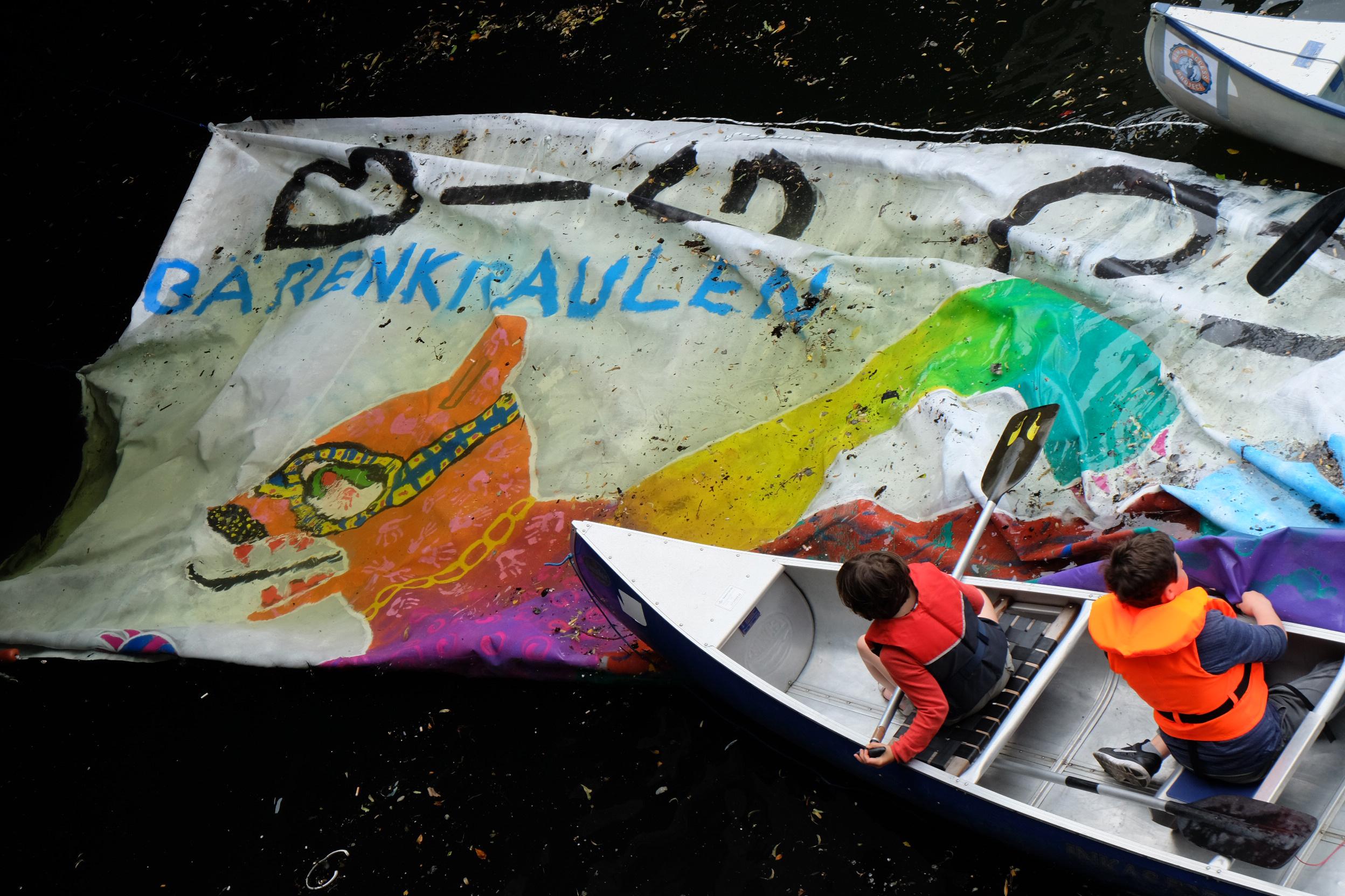 Kinder paddeln mit Kanu über ein Banner in der Spree