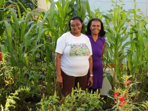 Two Women between corn and flowers in the AS-PTA garden.